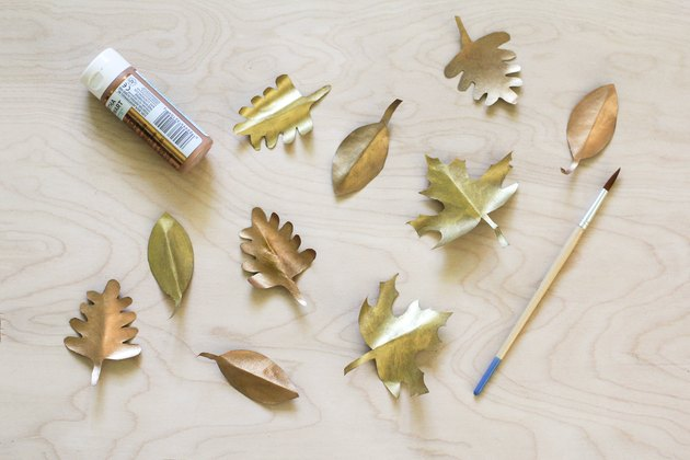 Painted gold paper leaves with paint brush and paint tube