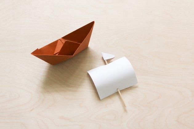 Bateau en papier brun plié avec voile en papier et cure-dent