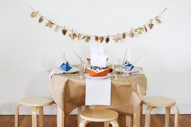 fall party idea with leafy garland, paper decor, and wood stools