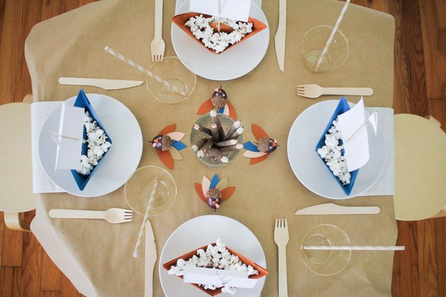 Kids table with paper tablecloth, disposable dishware, and paper decorations