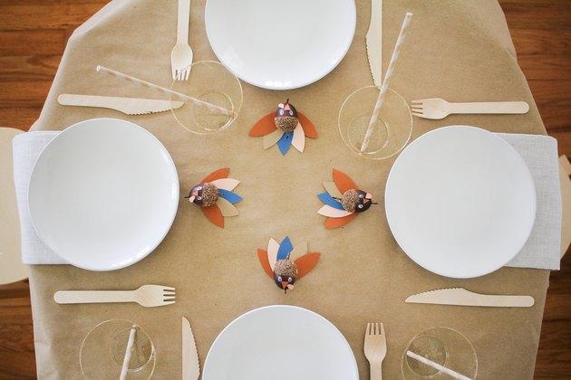Table à manger avec nappe en papier, ustensiles en bois et décor de dinde en gland de papier