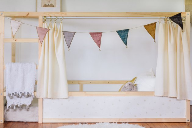 a kura bed frame that has been hacked by adding curtains and bunting and decorating surfaces with wallpaper