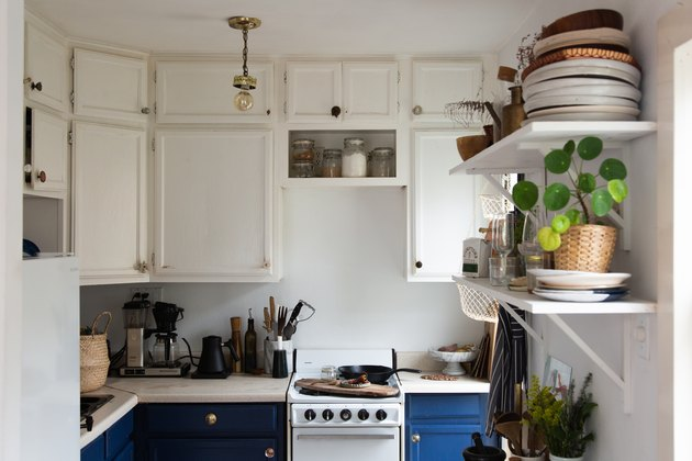 Eclectic kitchen with white overhead cabinets, blue lower cabinets, apartment size stove, open shelves, dishes, plants.