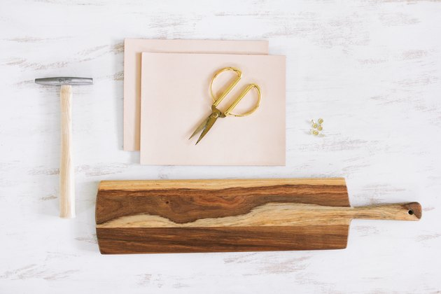 a paddle-shaped wooden cutting board, scissors, tacks, a tack hammer, and leather squares