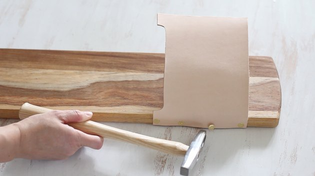 attaching leather strips to a cutting board with tacks