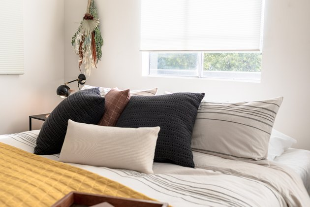 Bed with black and white pillows and yellow blanket