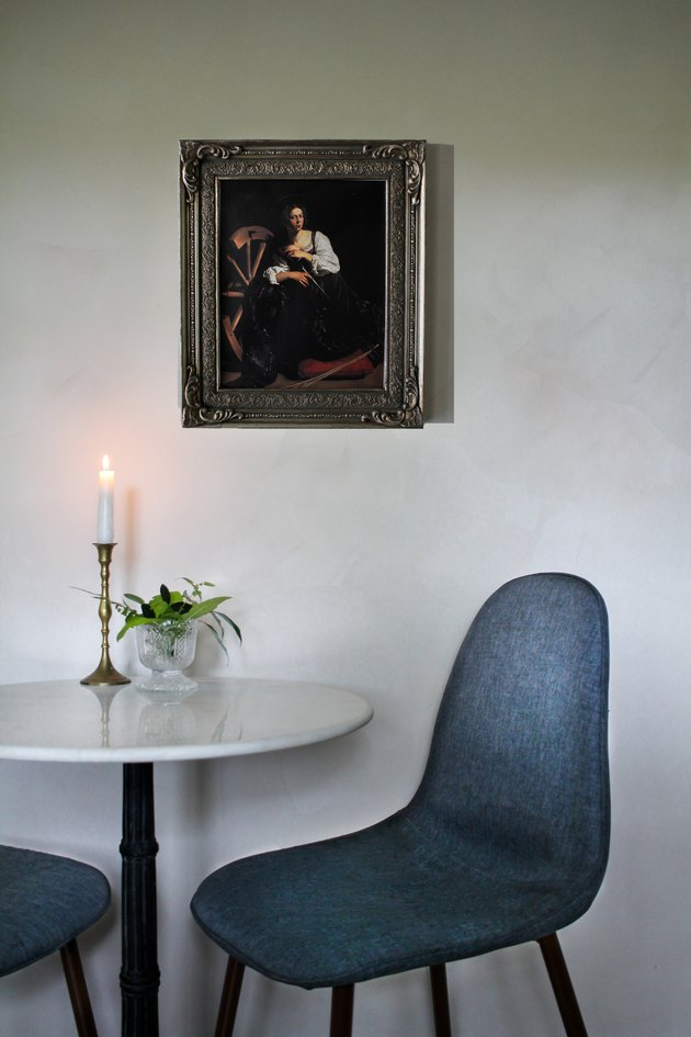 Table with lit candle and two blue chairs against white lime-washed wall with framed painting