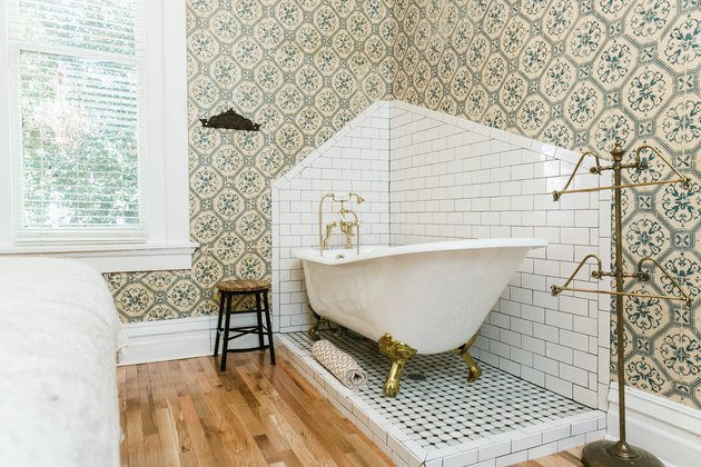 a claw-foot tub sits in a corner of a bathroom on a slightly raised penny tile platform