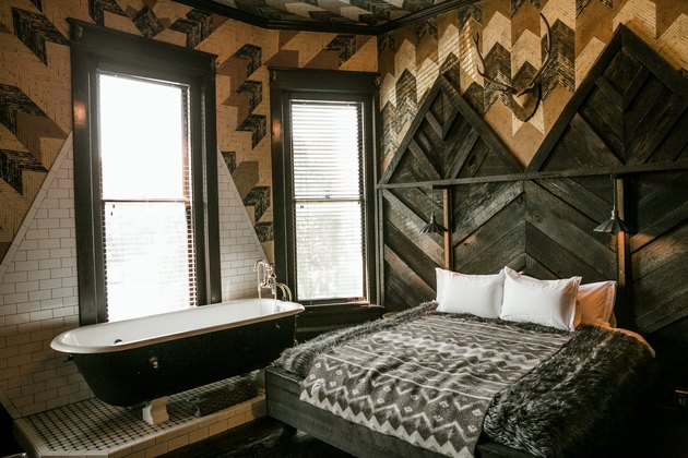 industrial farmhouse bedroom with wooden herringbone slats, chevron panels, and subway tile