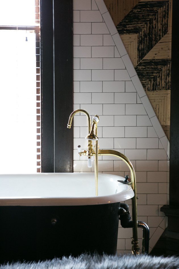 a porcelain tub with exposed brass taps next to a subway tile wall