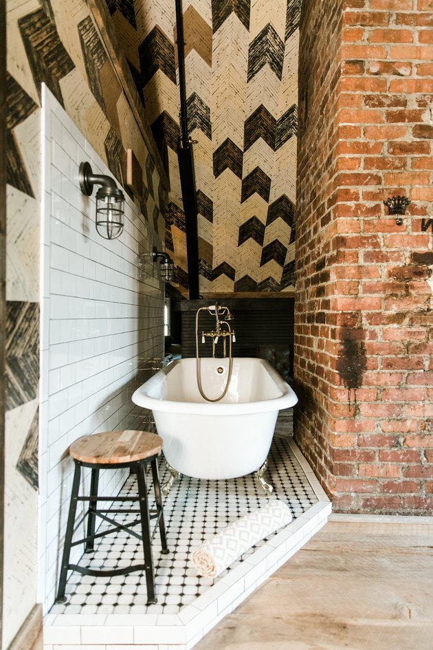 a clawfoot tub in a nook on a slightly raised tile platform in a bathroom with a herringbone tile ceiling