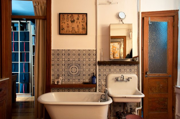 Rustic, old-fashioned style bathroom with white tub and sink, curtain, tiled walls, and wood door
