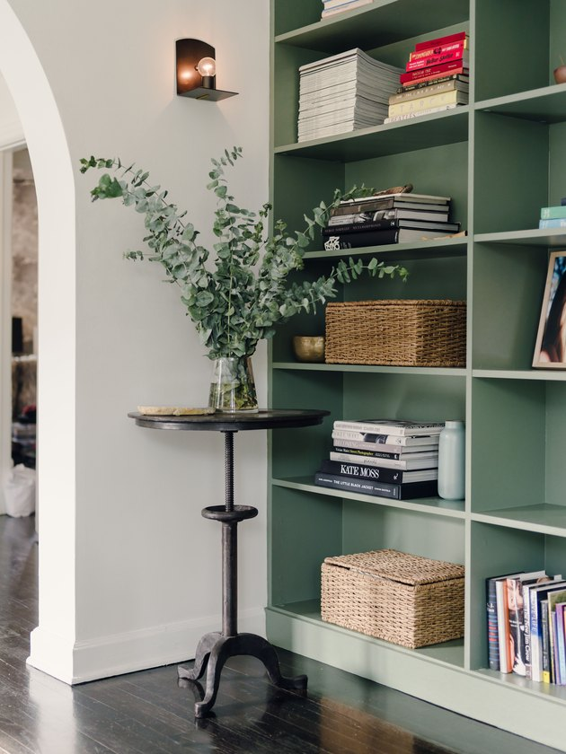 painted green built-in bookshelves styled with stacked booked and woven baskets