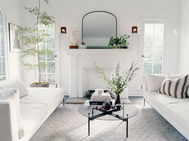 all white minimalist living room with two sofas facing each other, floor to ceiling windows, and a round glass coffee table
