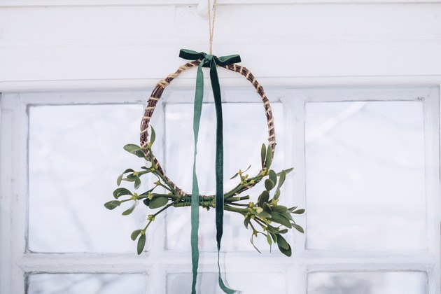 a finished diy mistletoe wreath with a green ribbon hangs from a ceiiing