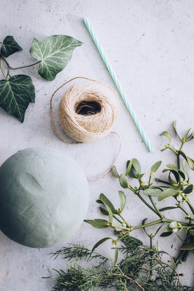 a foam floral ball, twine, a straw, mistletoe, and other greenery