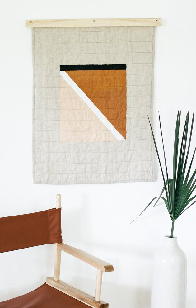 Painted quilt hanging with foldable brown chair and plant in vase
