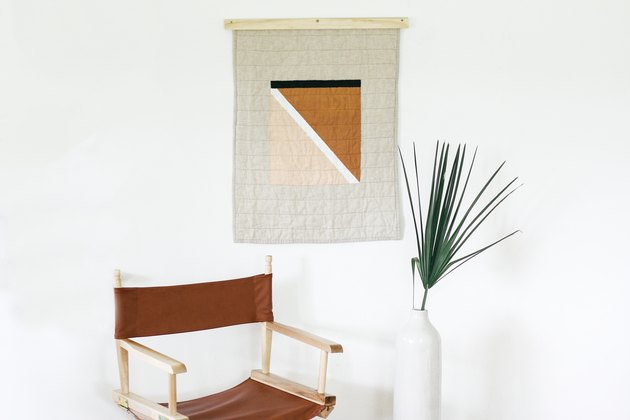 Painted quilt hanging with brown foldable chair and plant