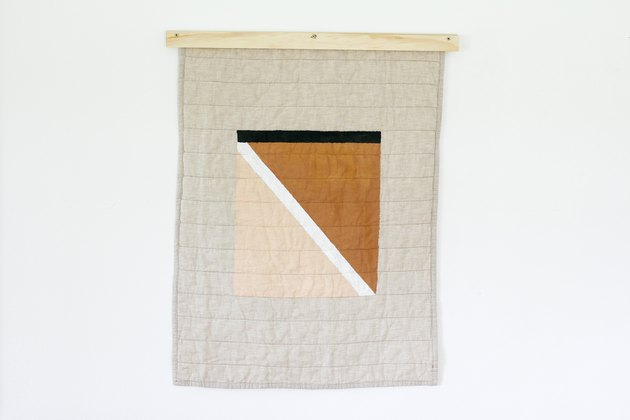White quilt with beige, brown, black pattern and wood beam