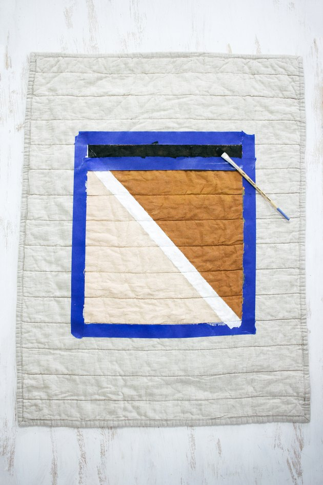Quilted pillow shame with blue painters tape around brown, black and white design
