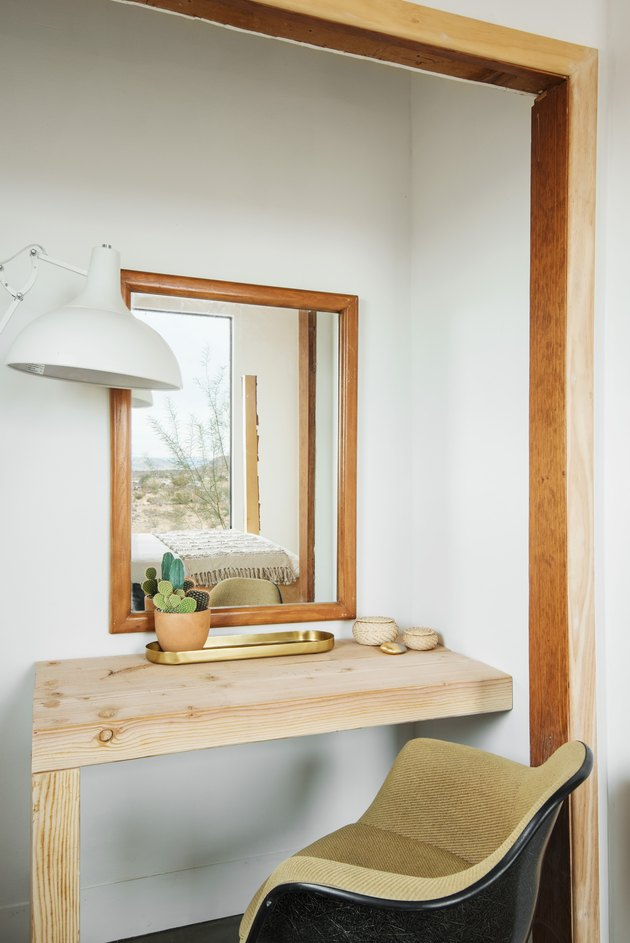 A wood desk with a plant and an office chair with a wood framed mirror