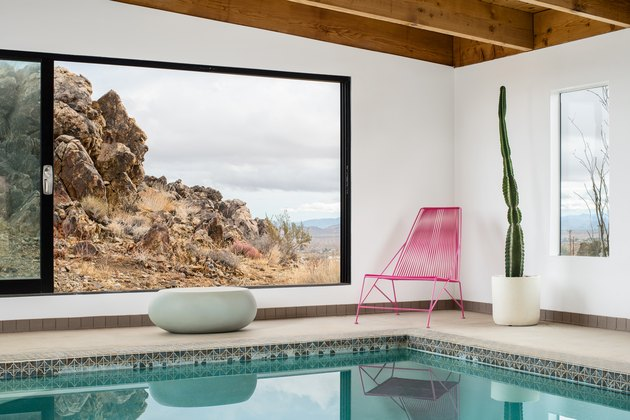 A pink metal chair with a cactus and large windows and a swimming pool