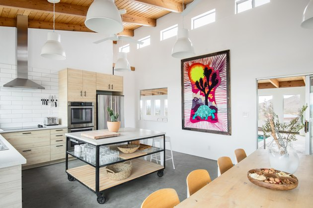 Minimalist kitchen with wood furniture, wood beam ceilings, stove vent, and colorful art