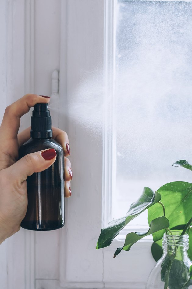 spraying the air with diy room spray