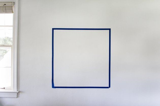 Blue painter's tape forming a square on a white wall next to window