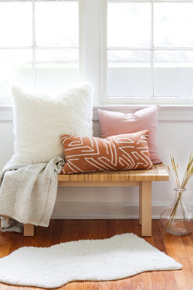 a white faux-fur pillow, a pink pillow, and an african-print pillow on a bench