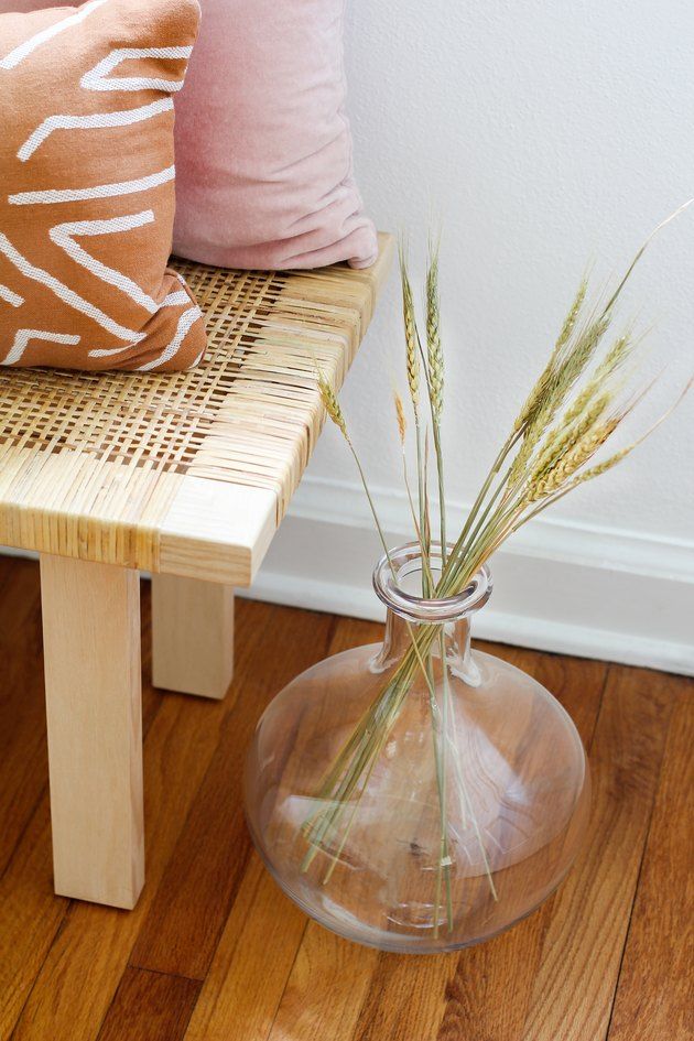 a globe-shaped glass vase full of dried grasses