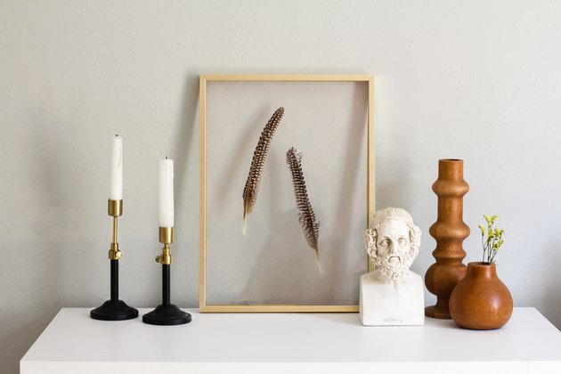 brass adjustable candlesticks next to a floating frame with feathers mounted in it and wooden bud holders