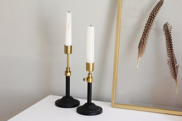 brass adjustable candlesticks next to a floating frame with feathers mounted in it