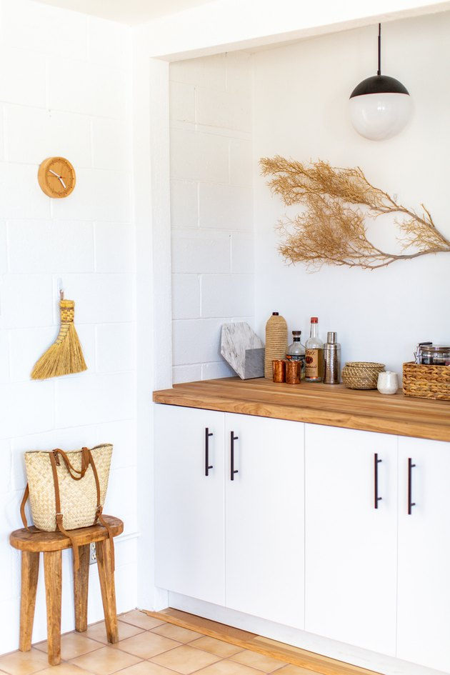 a decorative dried branch mounted on a wall above an appliance-filled wooden counter
