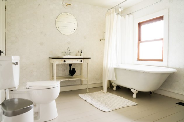 a bathroom with a rustic wooden vanity and a claw-foot tub