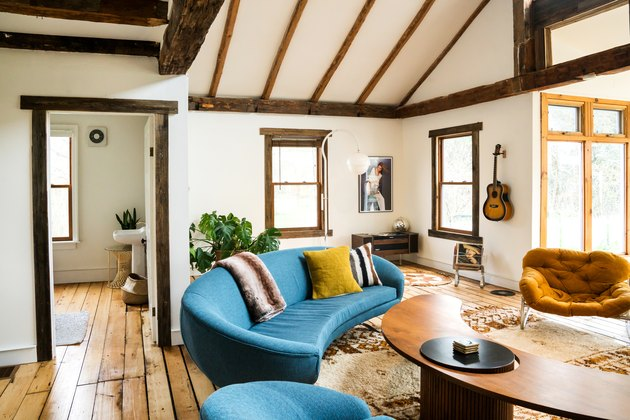 blue curved couches with a curved coffee table on a floor with rustic planks and a southwestern-patterned rug