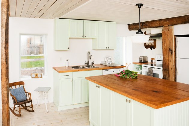 2021 kitchen color trend with a wooden ceiling, a pine-topped island, wood floors, green cabinets, and a wooden ceiling