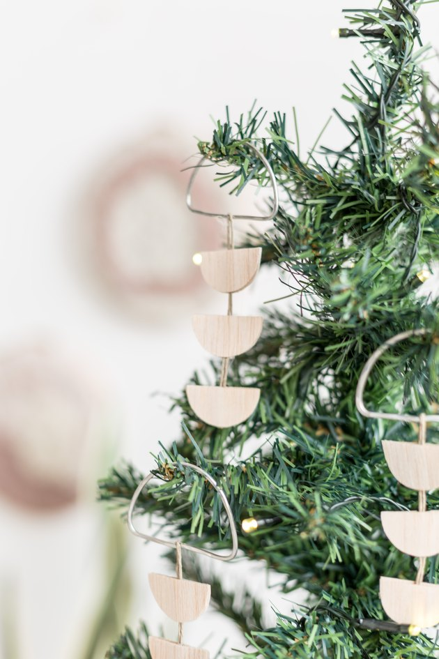 Scandi wood tree ornaments hanging off of small pine tree against white background