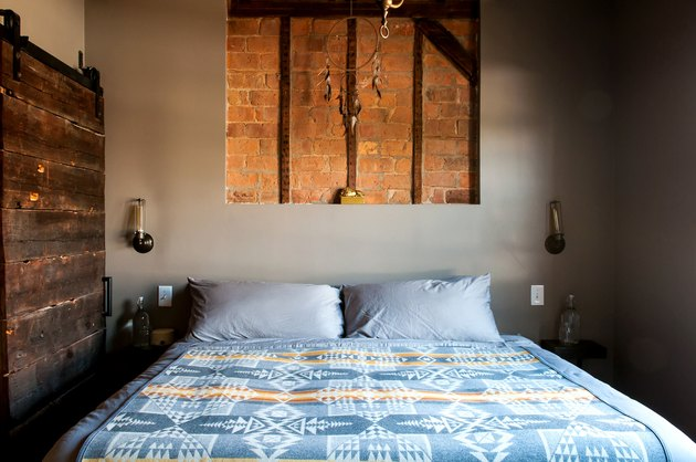 industrial farmhouse bed with a blue bedspread in a room with one wall sided with wooden planks and one in drywall with a cutout exposing brick