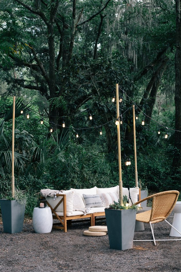 Round wicker chairs, white cushioned sofa, white stool and string lights