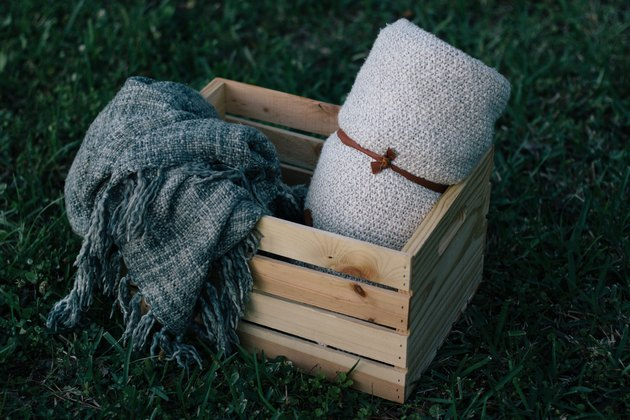 Outdoor storage and organization idea with a wood plywood crate with a gray blanket and a white blanket