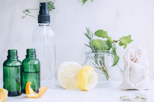 lemon, lemon peel, spray bottles, and mint leaves in a jar