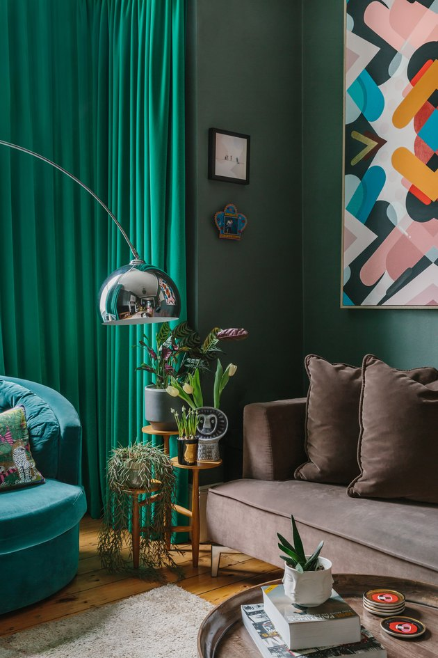 green walls in a living room with a brown couch and arc lamp