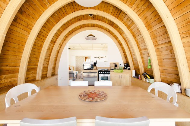 a dining room with curving wooden walls and ceiling that look like a ship's hull
