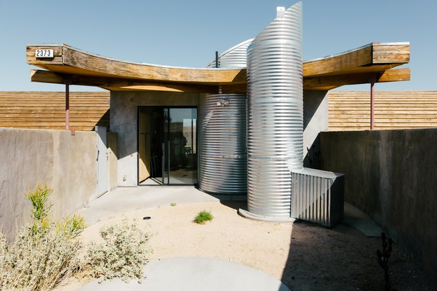 the back door of a futuristic house flanked by two vertical corrugated metal pipes