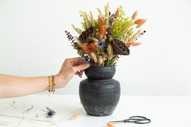 dried flowers in earthy fall colors, including lotus pods and bunny tails dyed burnt orange, in a black earthenware vase