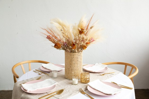 Cane vase with dried flowers on dining room table