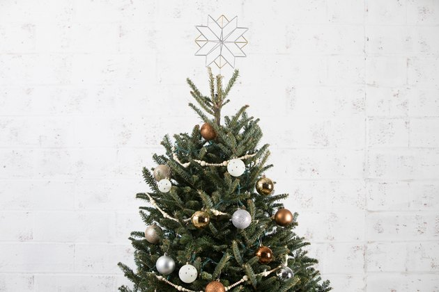 the top of a christmas tree decorated with ornaments, strings of beads, and a star