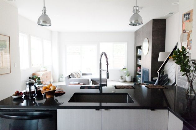 Kitchen with gray pendant lights, over a black-white kitchen island. French coffee press, bowl of oranges, and a clear vase of flowers.
