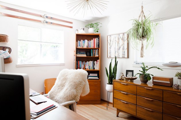 Office with sheepskin draped over desk chair, dresser, corner shelf, hanging plant with Home Office Desk Ideas